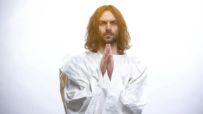 Jesus Christ praying in heaven light for world and humanity kindness, religion stock image