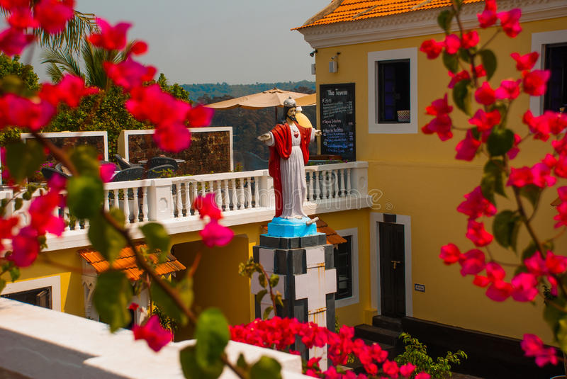 Jesus Christ statue. Fort Tiracol. Goa. India. Fort Tiracol. Statue of Jesus Christ on the background of red flowers. Goa. India stock photos