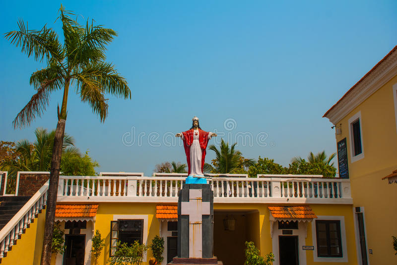 Jesus Christ statue. Fort Tiracol. Goa. India. Fort Tiracol. Catholic Church against the blue sky and palm trees. Goa. India royalty free stock images