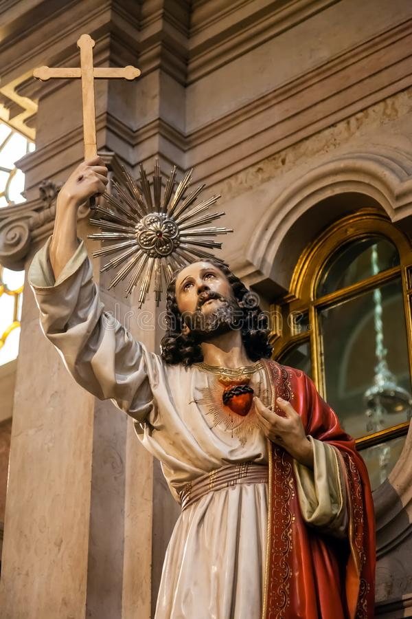 Jesus Christ statue holding Cross or Crucifix and Sacred Heart on chest. stock photography