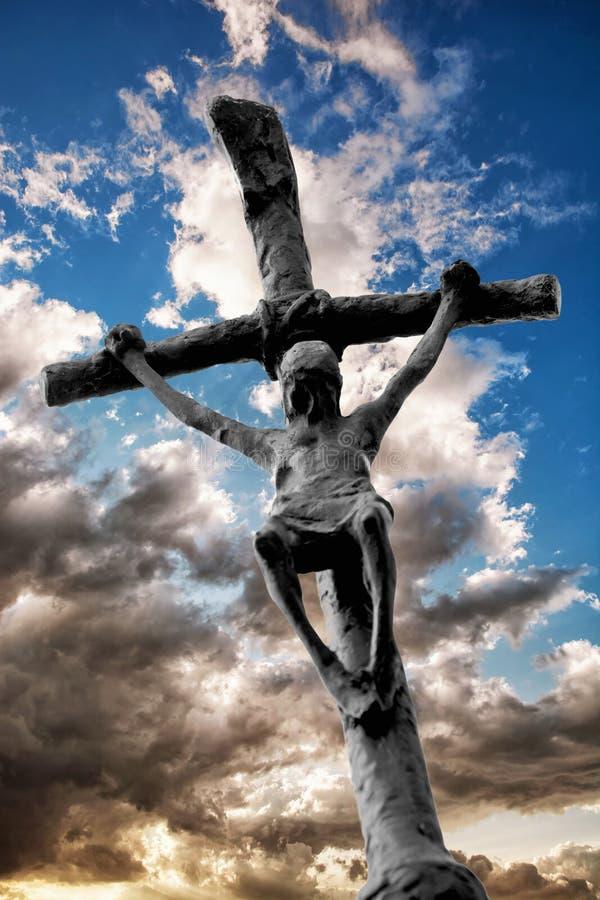 Jesus Christ sur la croix avec le ciel dramatique derrière lui photo libre de droits