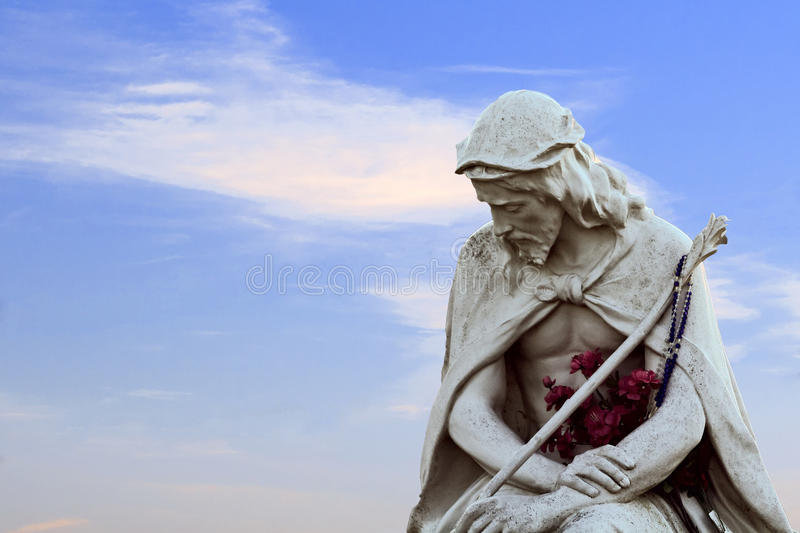 Jesus in Clouds. Sorrowful jesus statue with flowers on a blue sky with wispy clouds royalty free stock image