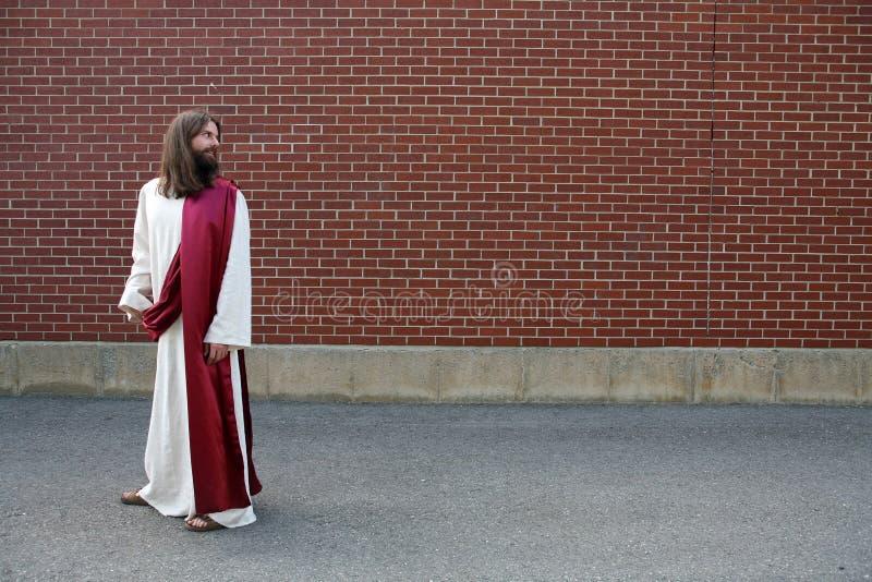 Jesus, der über seiner Schulter unbelegter Wand betrachtet stockfotografie