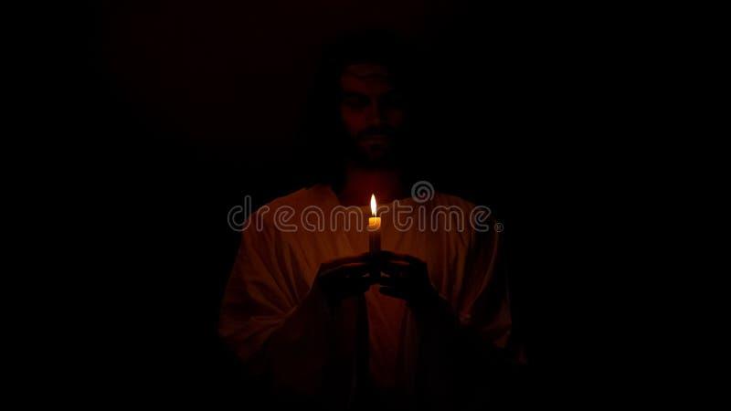 Jesus die in de kaars van de duisternisholding, boetedoening van zonden, geloof in redding bidden royalty-vrije stock foto's