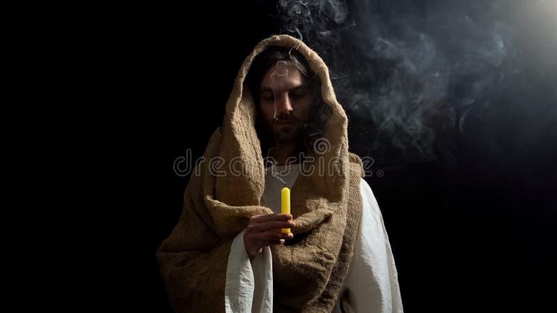 Jesus die geblazen kaars houden, die voor de boetedoening van mensenzonden, zielredding bidden stock fotografie