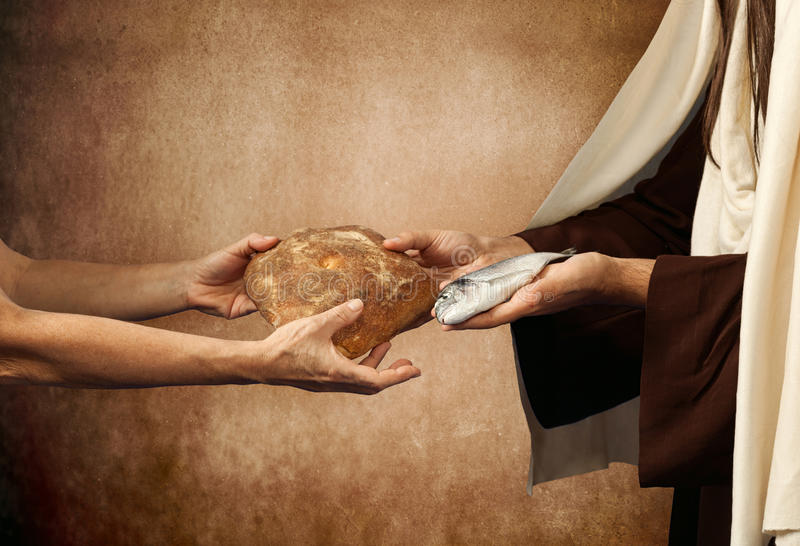 Jesus gives bread and fish stock photo