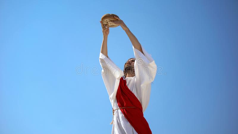Jesus God raising bread in hands to sky, blessing sacramental food, Eucharist. Stock photo royalty free stock photography