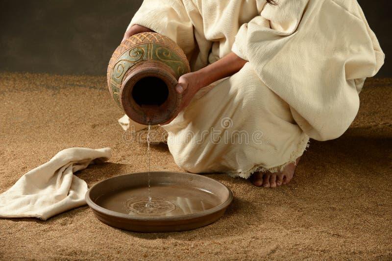 Jesus hällande vatten från en krus royaltyfri bild