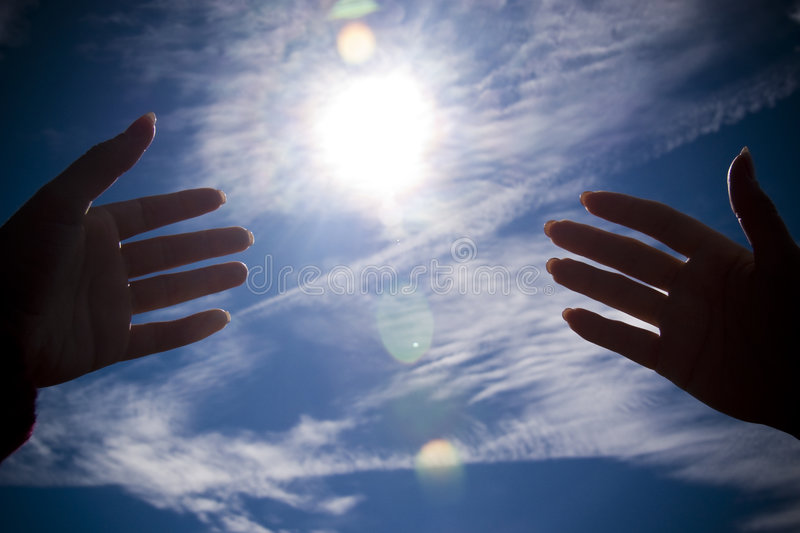 Jesus Hands. In the blue sky with sun flares and vignetting creating atmosphere stock photography