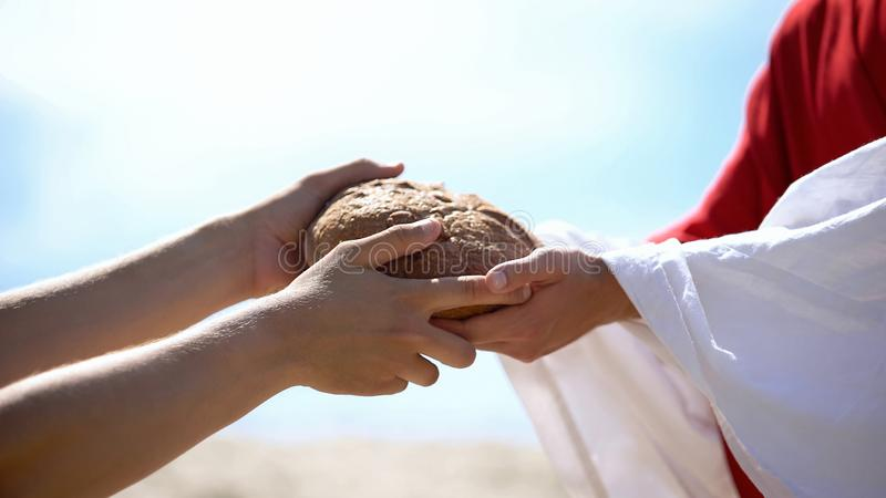 Jesus hands giving bread to poor man, biblical story to feed hungry, charity. Stock photo stock images