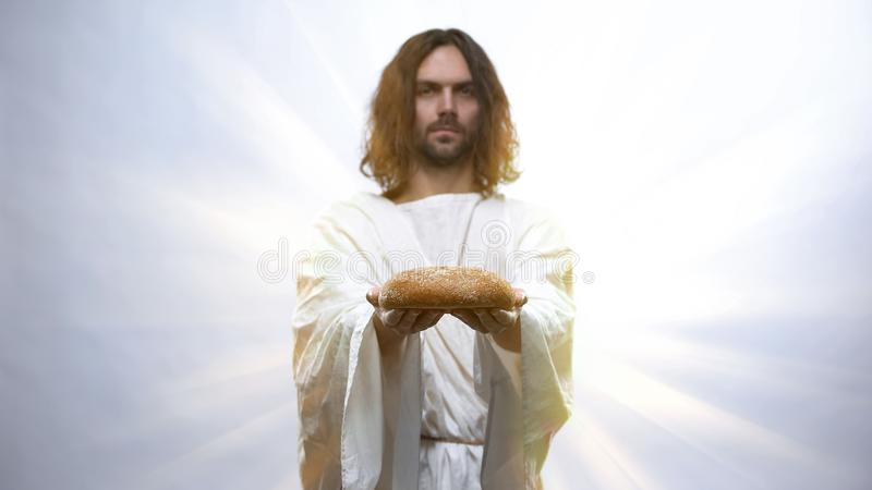 Jesus holding bread on illuminated background, sacramental food in religions. Stock photo stock images