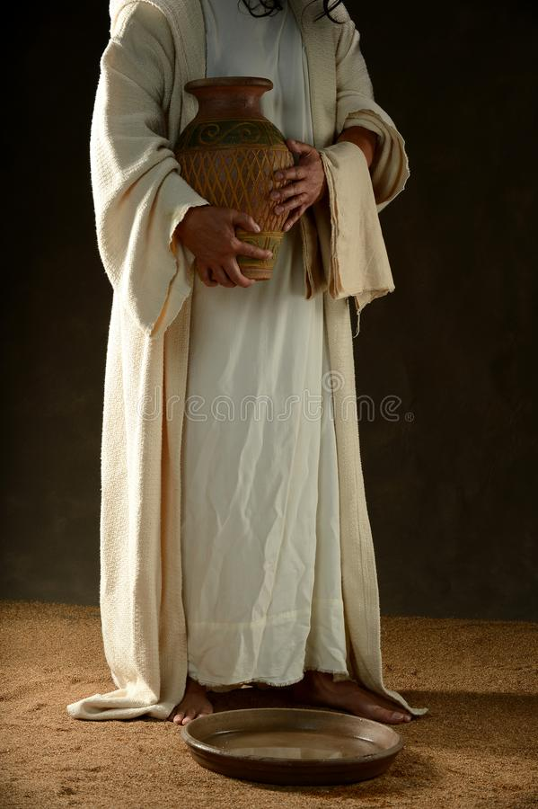 Jesus holding a jar of water standing up stock photo