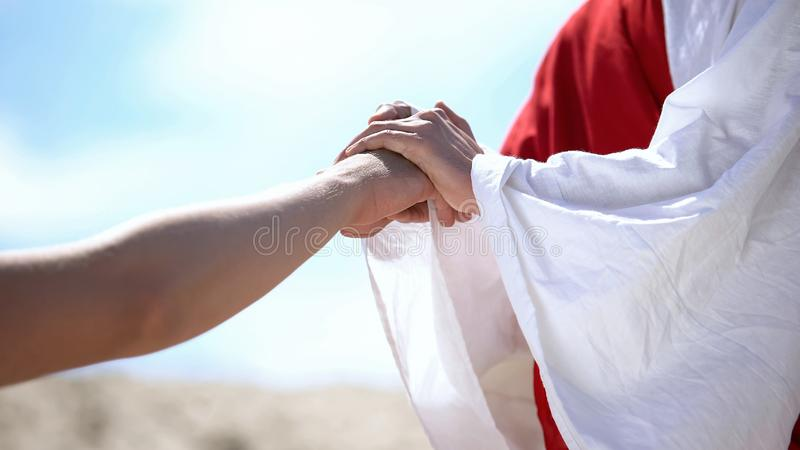 Jesus holding male hand to bless and heal Christian, religious miracle, closeup. Stock photo stock photos