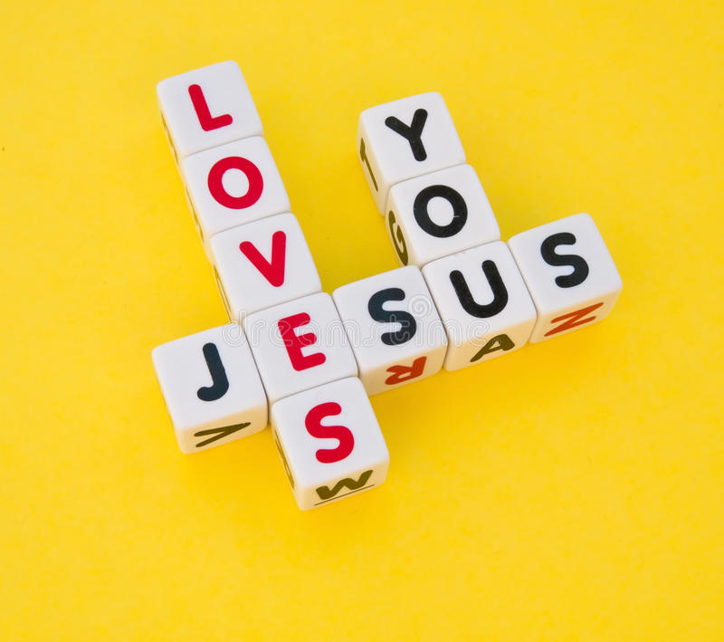 Jesus loves you. Text ' Jesus ', ' loves ' and ' you ' inscribed on small white cubes and arranged crossword style with common letters ' e and u ', yellow stock images