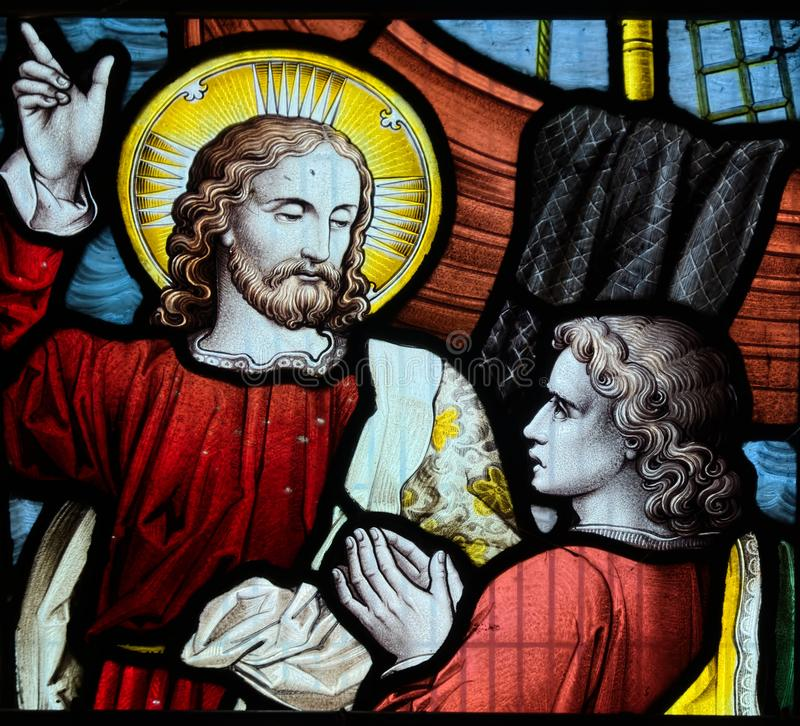 Jesus pointing to heaven. Stained glass window iconography royalty free stock image