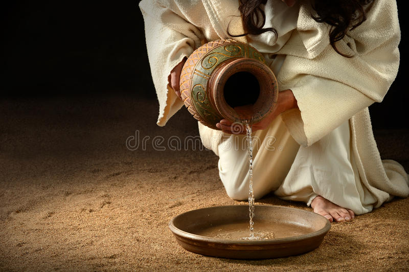 Jesus Pouring Water into Pan stock photo