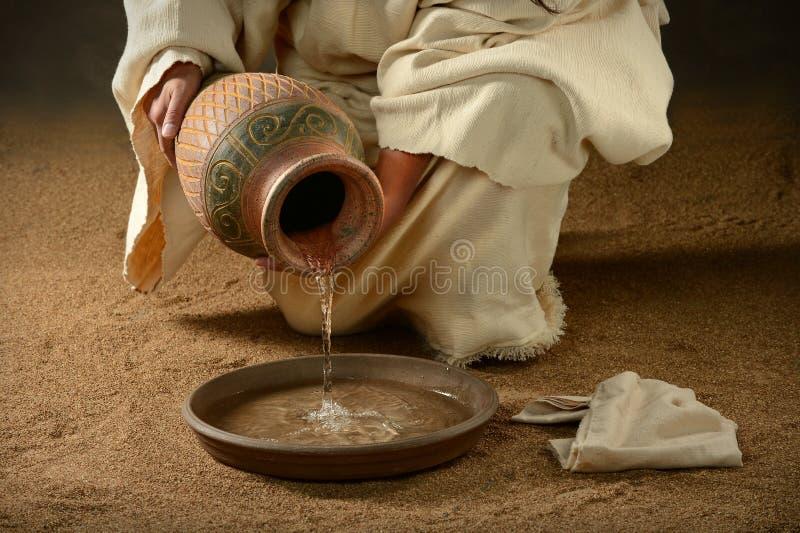 Jesus Pouring Water sulla pentola immagine stock libera da diritti