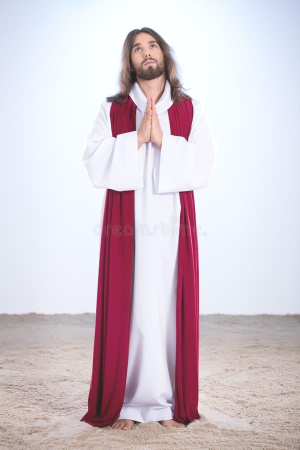 Jesus que reza na areia foto de stock