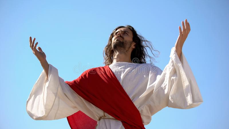Jesus raising hands to sky and praying, resurrection and ascension of Christ royalty free stock images