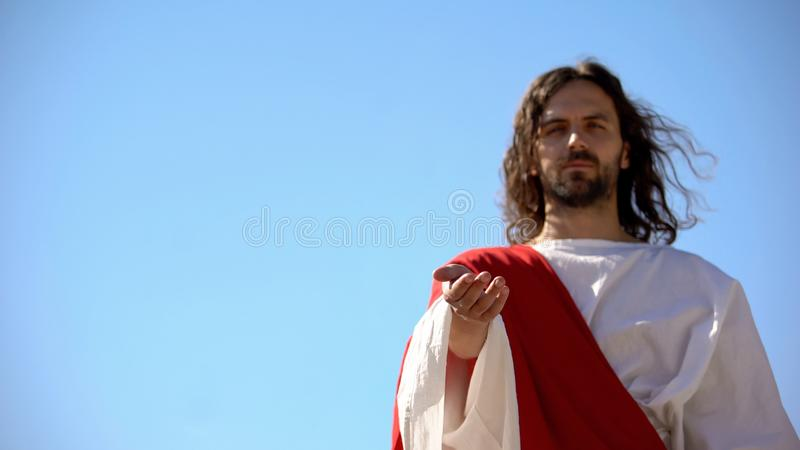 Jesus reaching out hand against blue sky, forgiveness and salvation of sinners stock image