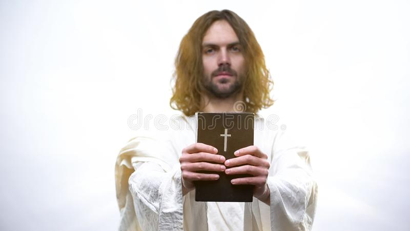 Jesus som ger den heliga bibeln och kräver bön, rättfärdig att leva i katolicism royaltyfria foton
