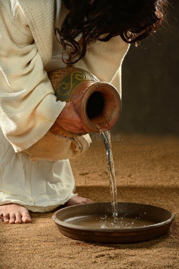 Jesus som häller vatten in i behållaren royaltyfri foto