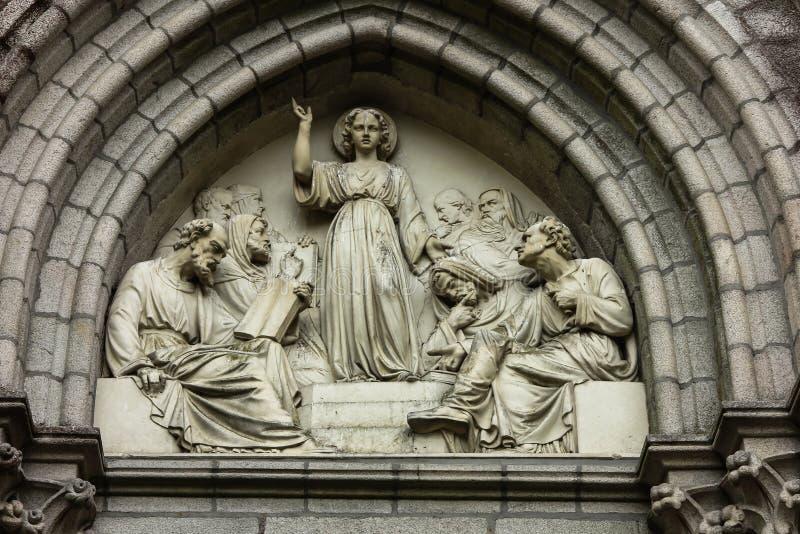 Jesus som vishet bland forskare, basrelief ovanför dörrkapellet av kloster av döttrarna av vishet i Helgon-Laurent-sur-Se royaltyfri bild