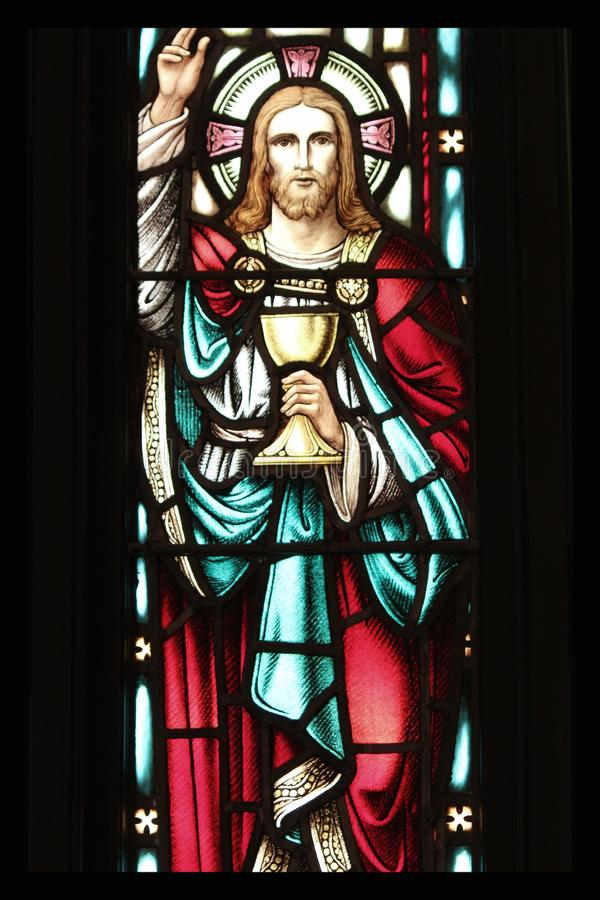 Jesus Stained Glass. Stained glass window depicting Jesus holding a communion chalice stock photo