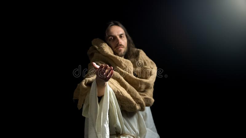 Jesus standing in darkness and giving helping hand, appeal to spirituality. Stock photo stock photos