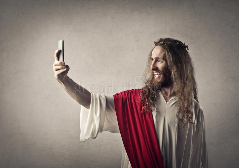 Jesus taking a selfie. Jesus with a phone and taking a selfie stock images