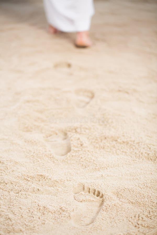 Jesus walking leaving footprints. Jesus walking leaving his footprints in sand royalty free stock photo
