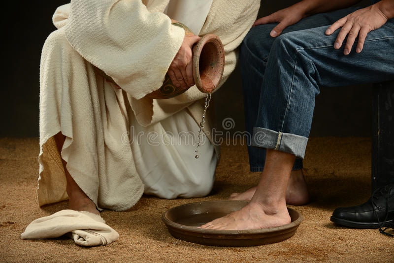 Jesus Washing Feet av mannen i jeans arkivbild