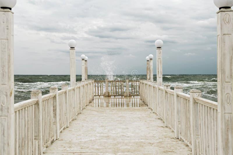Jetée avec les balustrades en bois blanches en mer pendant une tempête images stock