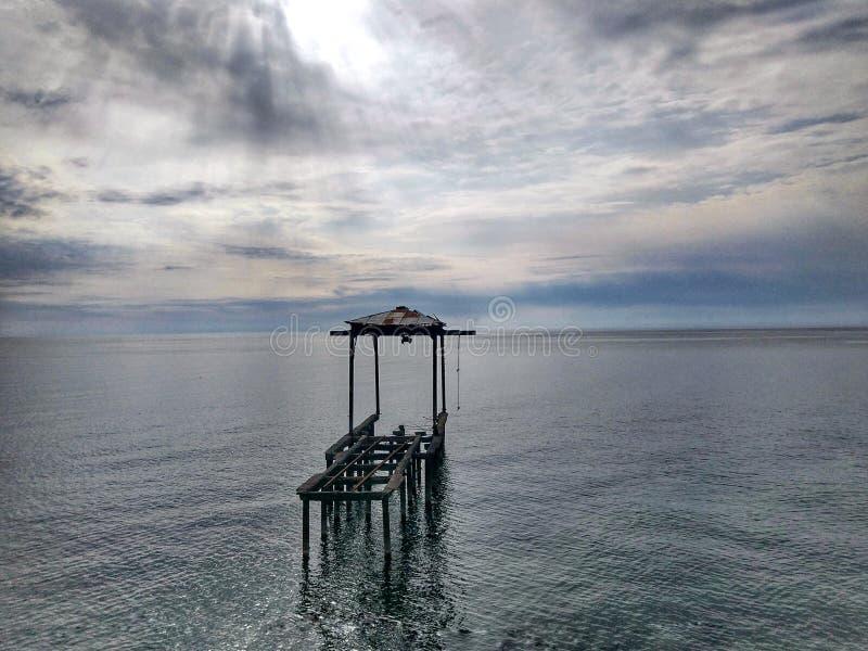 Jetée de mer isolée au coucher du soleil image libre de droits