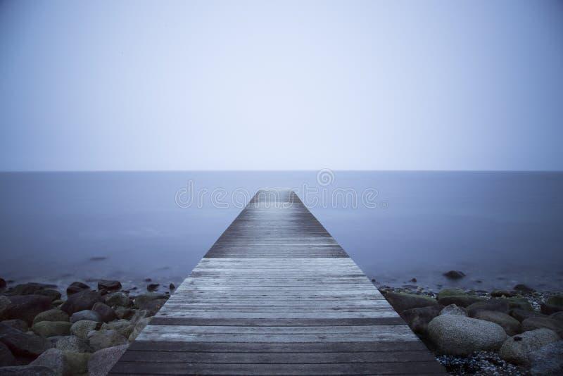 Jetée en bois avec de l'eau bleu images libres de droits