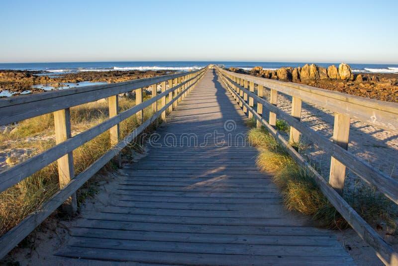 Jetée en bois avec l'herbe sur la côte de l'Océan Atlantique, Portugal La promenade en bois vers la mer sur des roches étayent Pa photographie stock
