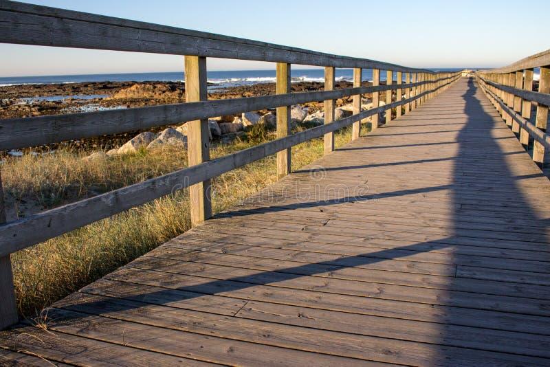 Jetée en bois avec l'herbe sur la côte de l'Océan Atlantique, Portugal La promenade en bois vers la mer sur des roches étayent Pa image stock