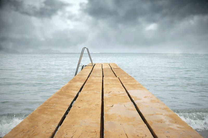 Jetée en bois avec la mer en jour sombre photos stock