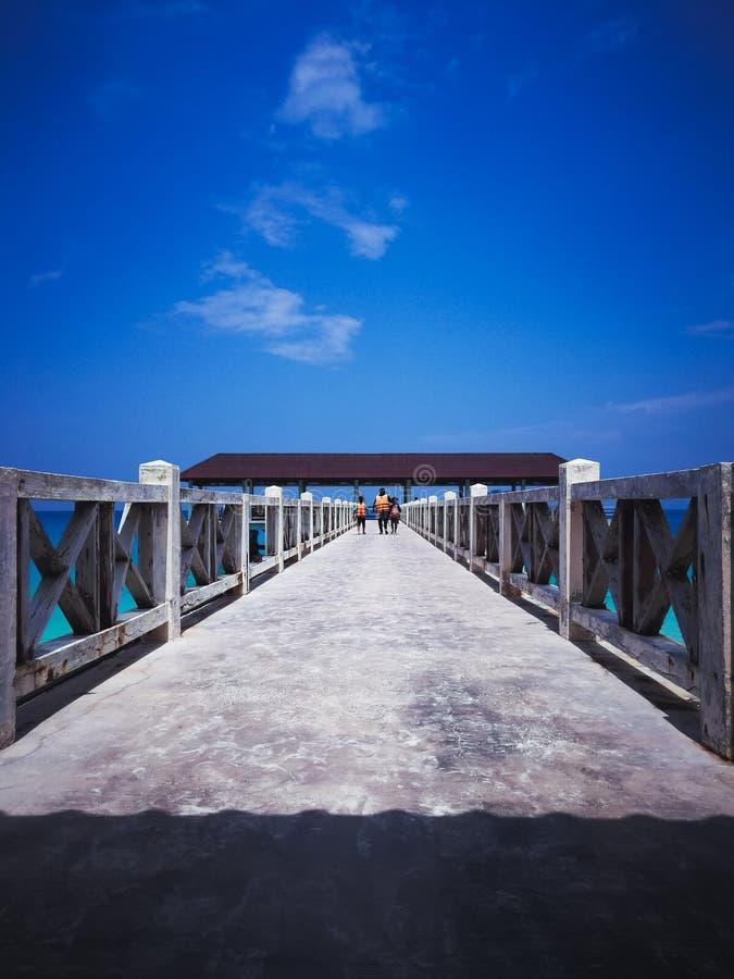 Jetée en bois dans le midi sous les cieux bleus clairs avec la marche de personnes photographie stock libre de droits