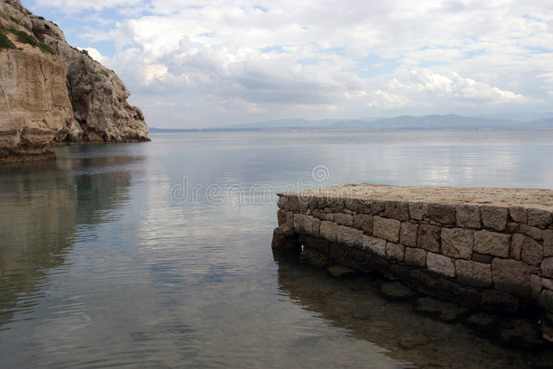 Jetée et roches en pierre sur la mer photos libres de droits