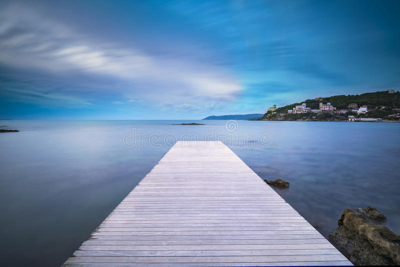 Jetée, roches et mer en bois de baie de Castiglioncello sur le coucher du soleil tuscan photos stock
