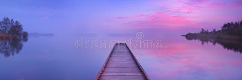 Jetée sur un lac immobile à l'aube aux Pays-Bas images libres de droits