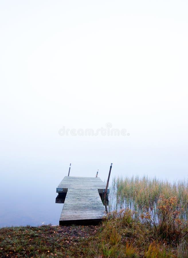 Jetée vide en rivière brumeuse photographie stock
