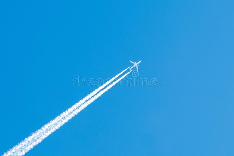 Jet Aircraft con los rastros gemelos de Vaper en un cielo azul claro foto de archivo