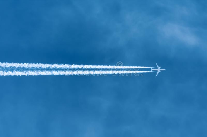 Jet aircraft flying at high altitude with contrails royalty free stock photography