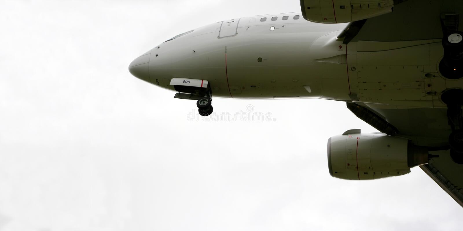 Jet airliner. Underside view of modern jet passenger airliner in flight with white sky background stock images