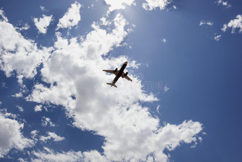 Jet Airliner sob nuvens quebradas em cima da aproximação fotografia de stock