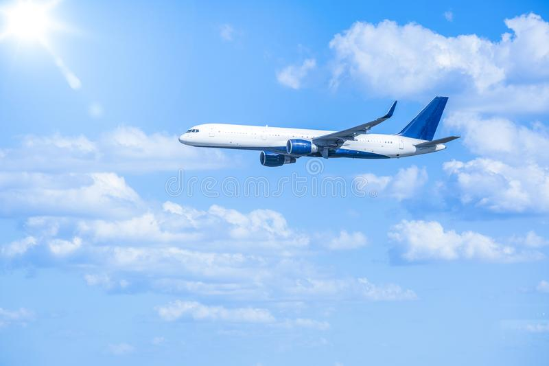 Jet Airplane flying through the blue sky on a sunny day. Large jet airplane flying in the sky full of clouds and the bright sun in the distance stock image