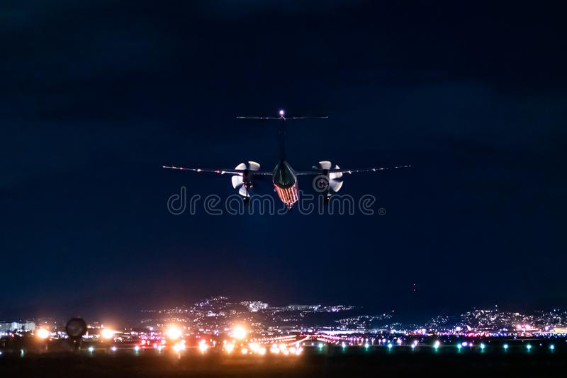 Propeller plane landing scene in the night royalty free stock photos