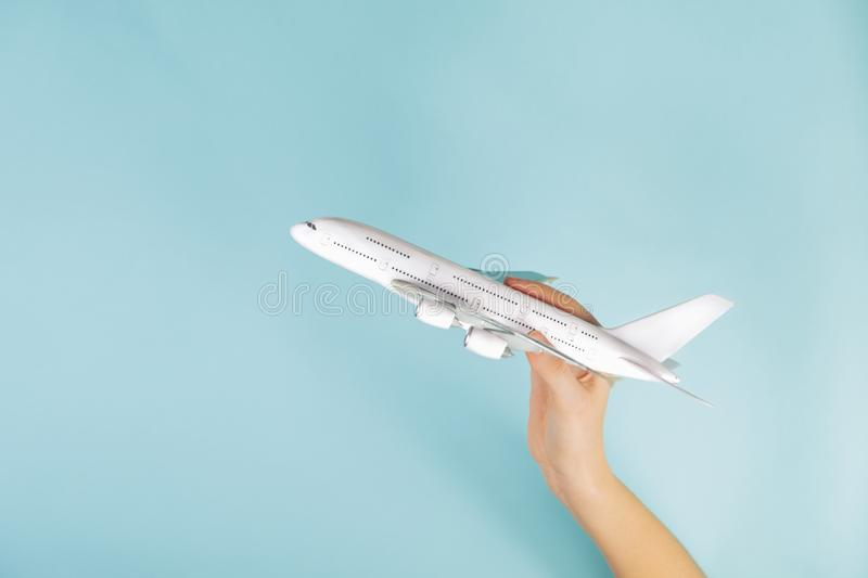 Jet airplane model in human hand on blue background. stock photo